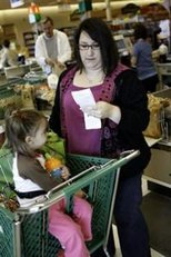 AP - Karen Wilmes of Hopkinton, R.I. checks out her savings while her daughter, Allison, waits, during a shopping trip ...